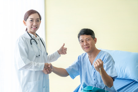 Asian female doctor at the hospital or clinic giving an handshake to hre patient, healthcare and professionalism concept
