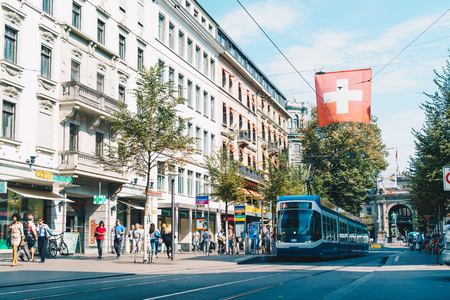 ZURICH, SWITZERLAND - AUG 23, 2018: A tram drives down the center of Bahnhofstrasse while people walk on the sidewalks in Zurich City, Switzerland.