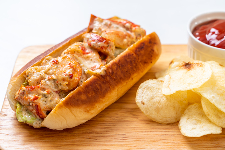 homemade lobster roll with potato chips on wooden board