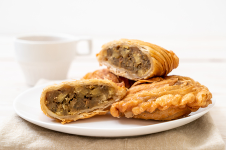 chicken curry puff pastry on wood background Фото со стока