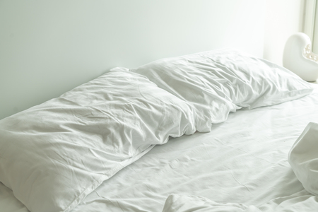 white pillow on bed and with wrinkle messy blanket in bedroom