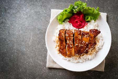 pollo a la parrilla con salsa teriyaki en un tazón de arroz cubierto