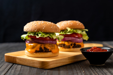 fresh tasty beef burger with cheese and ketchup on wood background Фото со стока