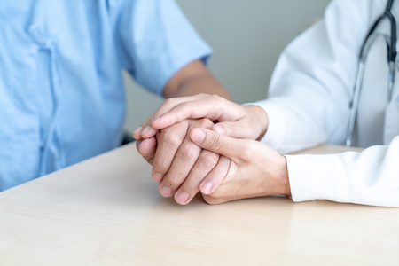 Hand of female doctor holding on her senior patient - selective focus point Stock Photo