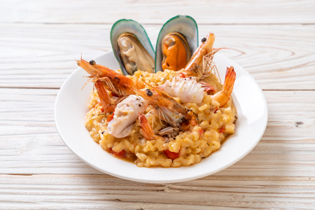 risotto with seafoods (shrimps, mussels, octopus, clams) and tomatoes - Italian food style 免版税图像