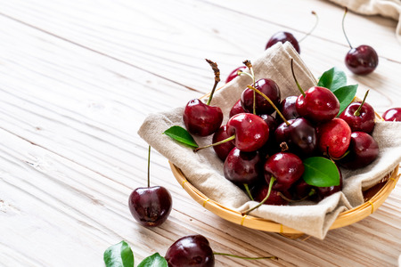 Fresh cherries in bowl  on wood background