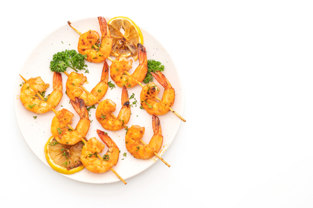 Grilled tiger shrimps skewers with lemon isolated on white background