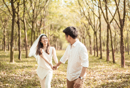 Happy Asian couple in love with tree arch at park 版權商用圖片