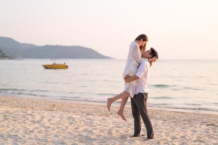 Szczęśliwa azjatycka para wybiera się w podróż poślubną na tropikalnej, piaszczystej plaży latem Zdjęcie Seryjne