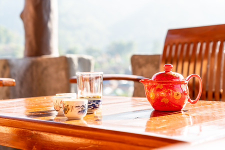 tea pot and cup in chinese style on the table with morning sunlight