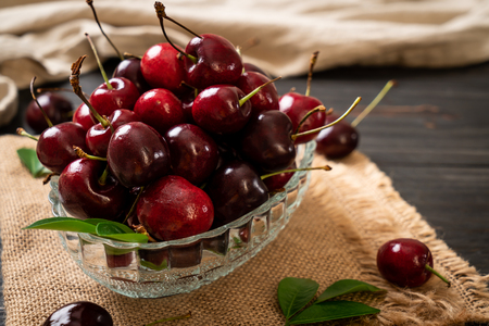 Fresh cherries in bowl  on wood background