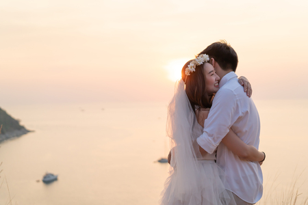 Happy young Asian couple in love having a good time with sea background Imagens