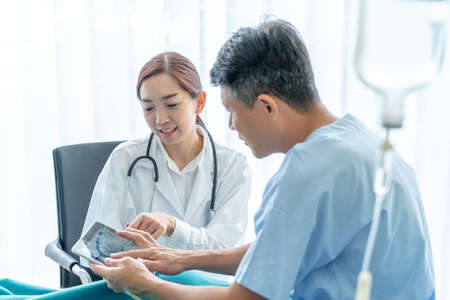 Asian female doctor and senior patient are consultation in hotpital room