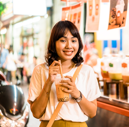 Happy Young Asian Woman Traveler with bubble tea at China Town in Bangkok, Thailand