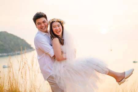 Happy young Asian couple in love having a good time with sea background