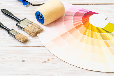 sample colors catalogue pantone or colour swatches book with paint roller brush Imagens