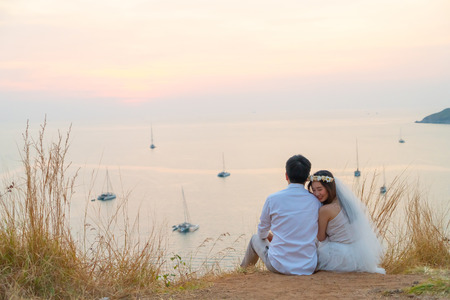 Happy young Asian couple in love having a good time with sea background 스톡 콘텐츠