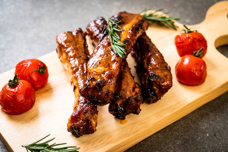 grilled barbecue ribs pork with rosemary and tomatoes