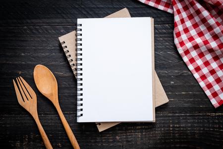 leeres Notizbuch für Textnotiz auf Holzoberfläche und Holzlöffel und -gabel mit Kopienraum