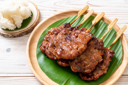 grilled skewered milk pork with white sticky rice - local Thai street food style Stock Photo