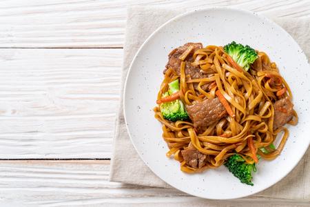fideos salteados con carne de cerdo y verduras - estilo de comida asiática
