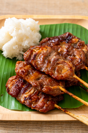 grilled skewered milk pork with white sticky rice - local Thai street food style Stockfoto
