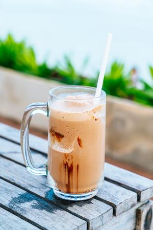 a glass of chocolate milkshake with sea view background Stockfoto