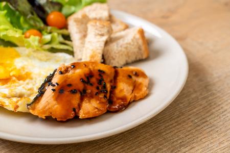 Filete de salmón teriyaki con huevo frito y ensalada - estilo de comida saludable Foto de archivo