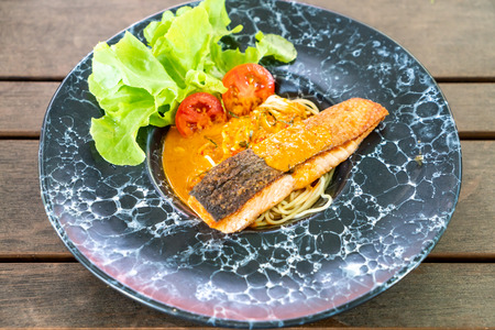 spaghetti with fried salmon on black plate 免版税图像