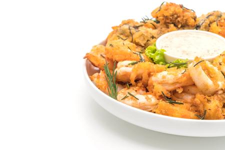 Gebratene Meeresfrüchte (Tintenfische, Garnelen, Muscheln) mit Sauce lokalisiert auf weißem Hintergrund Standard-Bild