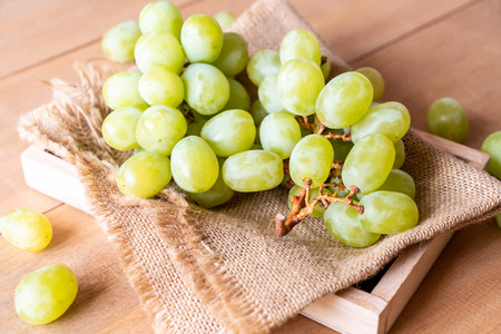 fresh green grapes on wood background Banque d'images - 122429505