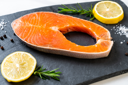 fresh raw salmon fillet steak with ingredient on board