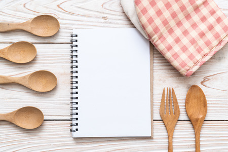 blank notebook for text note on wooden surface and wooden spoon and fork with copy sapce