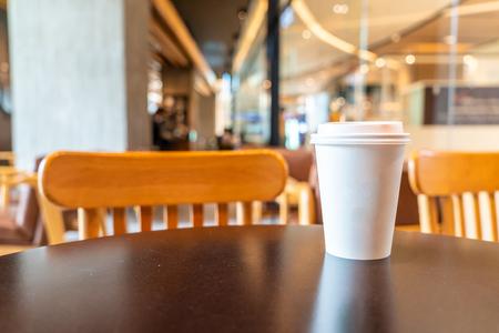 tasse de papier de café chaud dans un café et un café