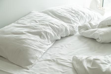 wit kussen op bed en met gerimpelde rommelige deken in slaapkamer Stockfoto