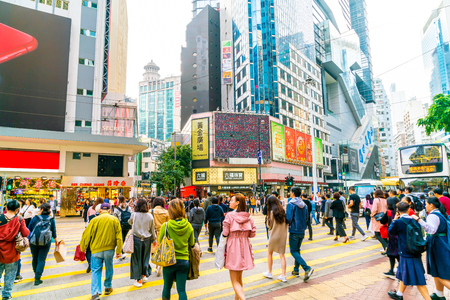 HONG KONG - FEB 21 2019: People walking across Hennessy Road, Causeway Bay with a big department store in Hong Kong.