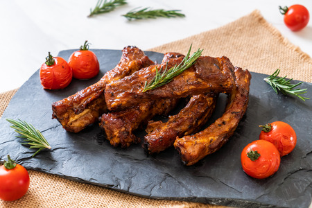 Grilled barbecue ribs pork with rosemary and tomatoes Stock Photo