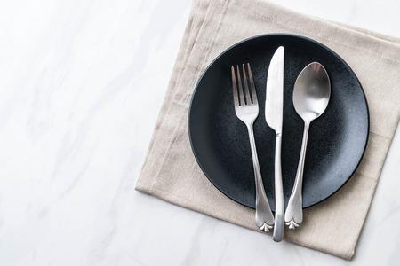 Plato vacío cuchara tenedor y cuchillo en la mesa