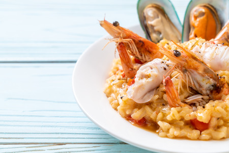 risotto with seafoods (shrimps, mussels, octopus, clams) and tomatoes - Italian food style