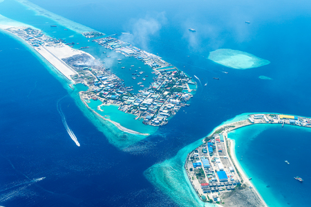 Maldives islands top view from airplane window with airplane's wing