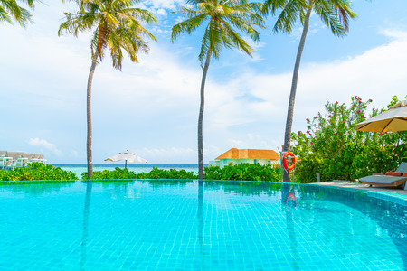 swimming pool with sea beach background in Maldives - holidays and vacation concept