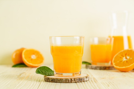 Fresh orange juice on wood background - healthy drink Stock Photo