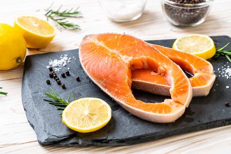 fresh raw salmon fillet steak with ingredient on board