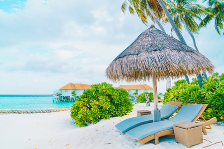 beach chair with tropical Maldives island  beach and sea - holiday vacation background concep Фото со стока