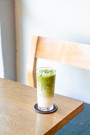 iced matcha green tea with milk on wood table in cafe restaurant Stock Photo