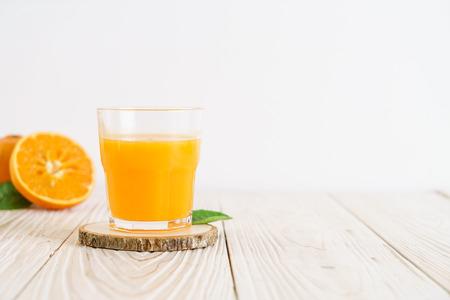 Fresh orange juice on wood background - healthy drink