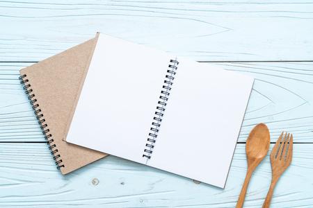 taccuino vuoto per nota di testo su superficie di legno e cucchiaio e forchetta di legno con copia spazio