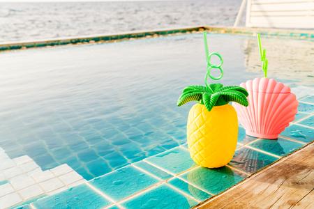 在游泳池和海背景旁边的热带夏天饮料