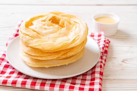 fried crispy roti dough with sweetened condensed milk Фото со стока