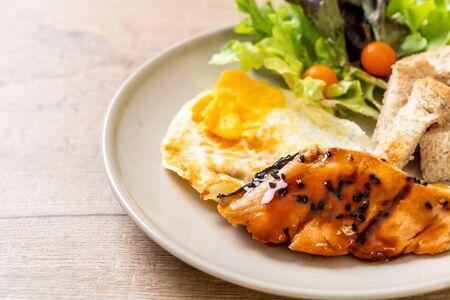 salmon teriyaki steak with fried egg and salad - healthy food style Фото со стока